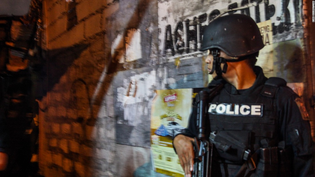 """An armed officer accompanies a """"knock and plead"""" operation in the Bangaray Labis slum in Quezon City."""