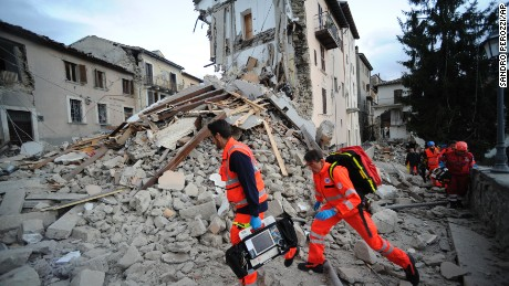 Rescuers search a crumbled building in Arcuata del Tronto, central Italy, where a 6.1 earthquake struck just after 3:30 a.m., Wednesday, Aug. 24, 2016. The quake was felt across a broad section of central Italy, including the capital Rome where people in homes in the historic center felt a long swaying followed by aftershocks. (AP Photo/Sandro Perozzi)