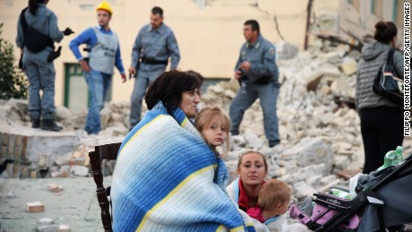 Victims sit among the rubble of a house after a strong heartquake hit Amatrice on August 24, 2016. Central Italy was struck by a powerful, 6.2-magnitude earthquake in the early hours, which has killed at least three people and devastated dozens of mountain villages. Numerous buildings had collapsed in communities close to the epicenter of the quake near the town of Norcia in the region of Umbria, witnesses told Italian media, with an increase in the death toll highly likely.