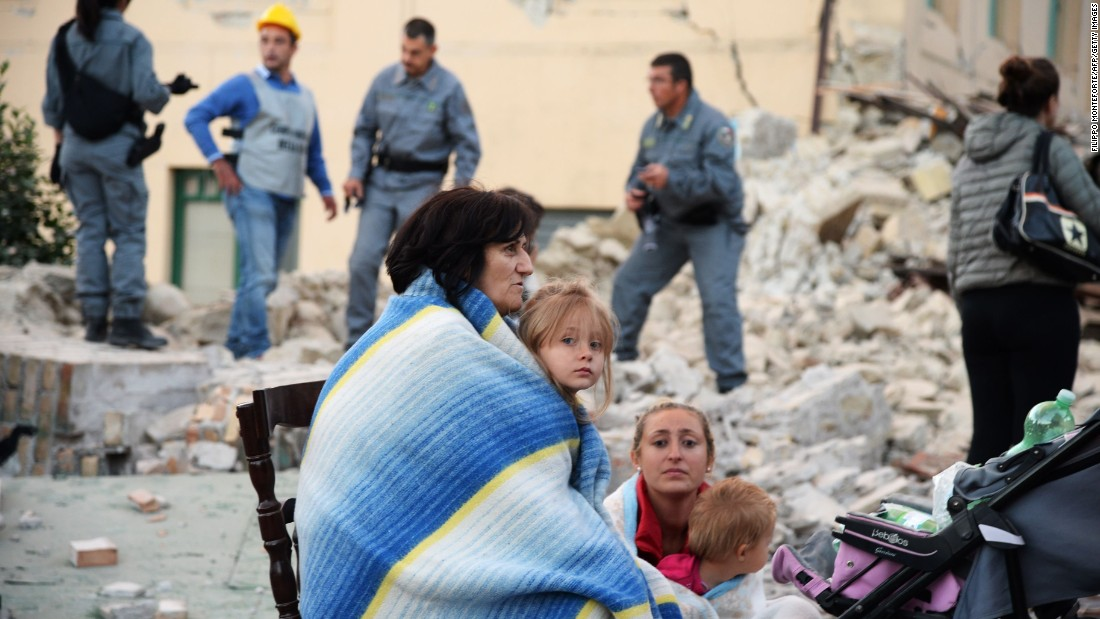 Survivors sit among the rubble of a house in Amatrice on August 24.
