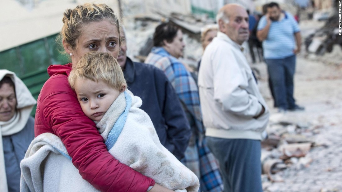 A woman tries to comfort her child in Amatrice on August 24.