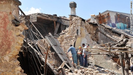 Residents inspect the rubble of buildings destroyed by an earthquake on April 6, 2009 in Onna, Italy.