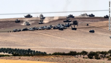 This picture taken from the Turkish Syrian border city of Karkamis in the southern region of Gaziantep, on August 24, 2016 shows Turkish army tanks and pro-Ankara Syrian opposition fighters moving two kilometres west from the Syrian Turkish border town of Jarabulus.  Turkey's army backed by international coalition air strikes launched an operation involving fighter jets and elite ground troops to drive Islamic State jihadists out of a key Syrian border town. Turkey's state-run Anadolu news agency reported that pro-Ankara Free Syrian Army (FSA) rebels had already penetrated three kilometres (two miles) inside Syria towards the IS-held town of Jarabulus. The air and ground operation, the most ambitious launched by Turkey in the Syria conflict, is aimed at clearing jihadists from the town of Jarabulus, which lies directly opposite the Turkish town of Karkamis. / AFP PHOTO / BULENT KILICBULENT KILIC/AFP/Getty Images