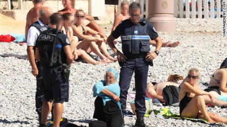 Police patrolling the promenade des anglais beach in Nice fine a woman for wearing a burkini on August 24, 2016.
