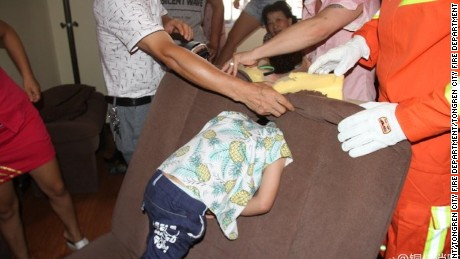 People crowd around a four-year-old boy who got his head stuck in a sofa.