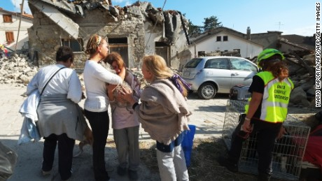 Women cry in front of damaged houses in a street in the central Italian village of Illica, near Accumoli, on August 24, 2016 after a powerful earthquake rocked central Italy. A powerful pre-dawn earthquake devastated mountain villages in central Italy on August 24, 2016, leaving at least 73 people dead, dozens more injured or trapped under the rubble and thousands temporarily homeless. Scores of buildings were reduced to dusty piles of masonry in communities close to the epicentre of the pre-dawn quake, which had a magnitude of between 6.0 and 6.2, according to monitors.   / AFP / MARIO LAPORTA        (Photo credit should read MARIO LAPORTA/AFP/Getty Images)