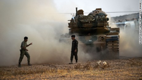 This picture taken around 5 kilometres west from the Turkish Syrian border city of Karkamis in the southern region of Gaziantep, on August 25, 2016 shows Turkish Army soldiers standing next a to tank.Turkey's army backed by international coalition air strikes launched an operation involving fighter jets and elite ground troops to drive Islamic State jihadists out of a key Syrian border town. The air and ground operation, the most ambitious launched by Turkey in the Syria conflict, is aimed at clearing jihadists from the town of Jarabulus, which lies directly opposite the Turkish town of Karkamis. / AFP PHOTO / BULENT KILICBULENT KILIC/AFP/Getty Images