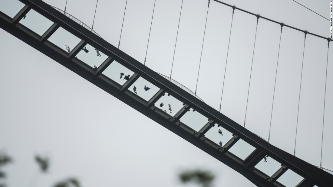 People stand on the world's highest and longest glass-bottomed bridge in Zhangjiajie, China, on Saturday, August 20.