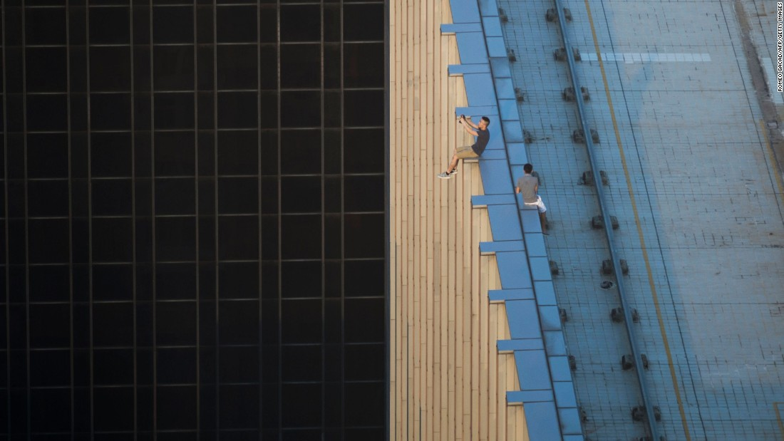 People take photos as they sit on the ledge of a high-rise building in Hong Kong on Tuesday, August 23.