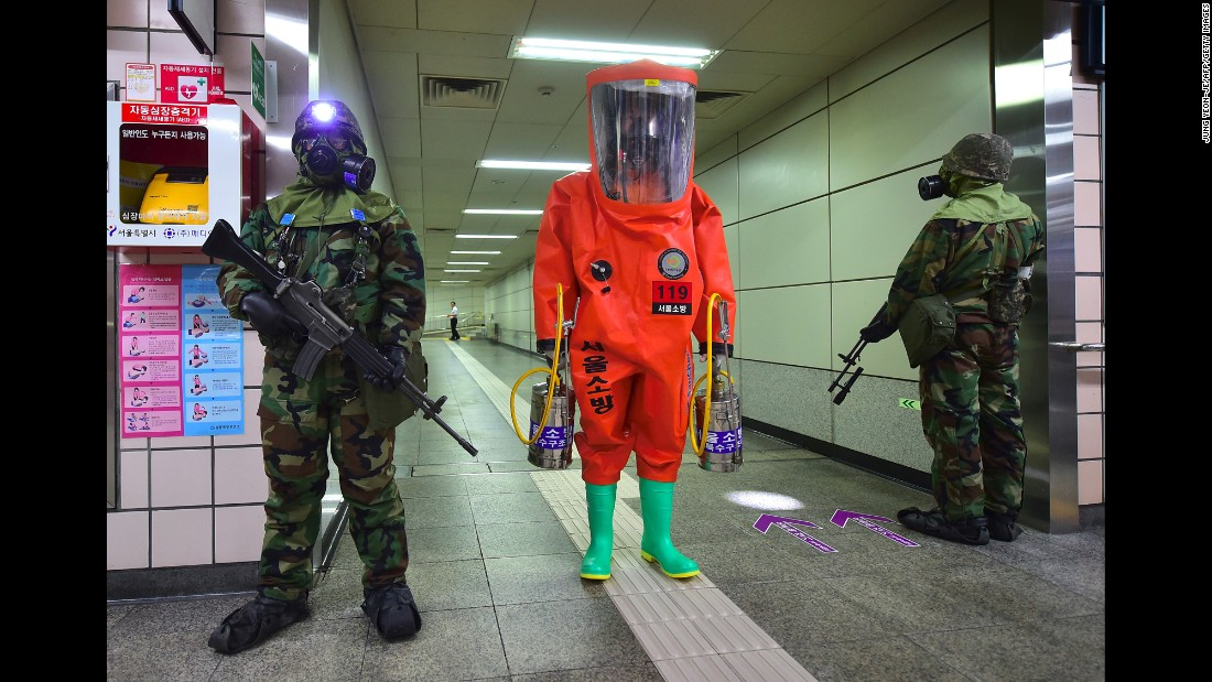 A person wearing full protective gear, center, stands with soldiers wearing gas masks during a joint South Korea-US anti-terror drill at a subway station in Seoul, South Korea, on Tuesday, August 23.