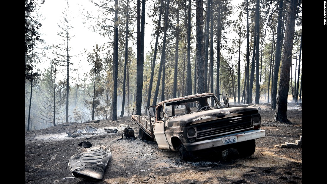 """A charred truck is seen near the home of Julie and Art Thayer near Valleyford, Washington, on Monday, August 22. The Thayers had been hiking over the weekend and returned home Sunday night to find their home destroyed. Wildfires in the Spokane area have destroyed more than a dozen homes, <a href=""""http://bigstory.ap.org/article/aa79c2dc9bd147a0ad0edc2560338a3e/crews-battle-blazes-california-washington-state-wyoming"""" target=""""_blank"""">according to The Associated Press</a>."""