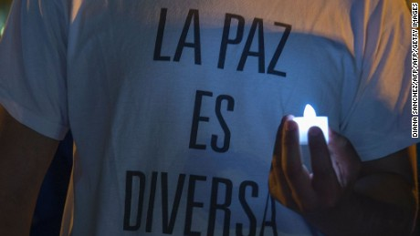"""A man wearing a t-shirt reading """"peace is diverse"""" takes part in a protest against homophobia in Bogota, Colombia, on August 16, 2016. / AFP / Diana SANCHEZ        (Photo credit should read DIANA SANCHEZ/AFP/Getty Images)"""