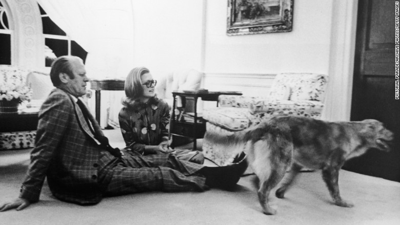 Ford sits with his daughter Susan on the floor of the White House's Great Hall, watching their pet golden retriever Liberty, circa 1978.