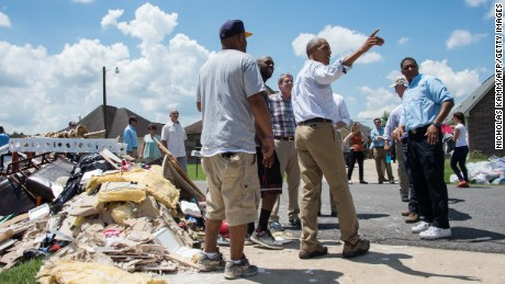 US President Barack Obama speaks with residents as he tours a flood-affected area in Baton Rouge, Louisiana, on August 23, 2016. / AFP / NICHOLAS KAMM        (Photo credit should read NICHOLAS KAMM/AFP/Getty Images)