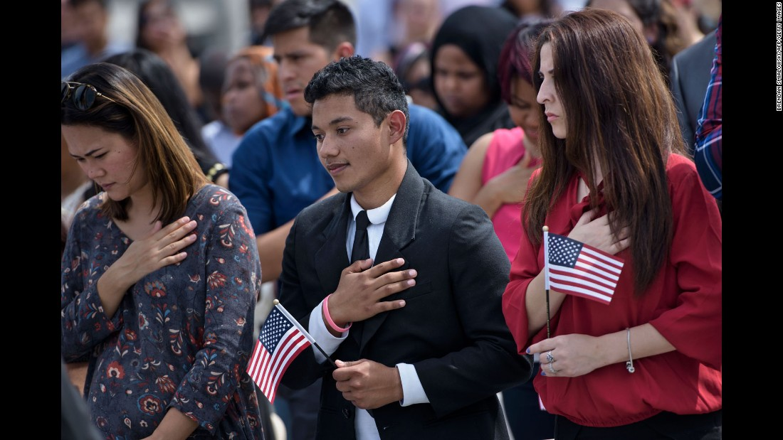 People listen to the United States national anthem during a naturalization ceremony at the National Mall in Washington on Thursday, August 25.