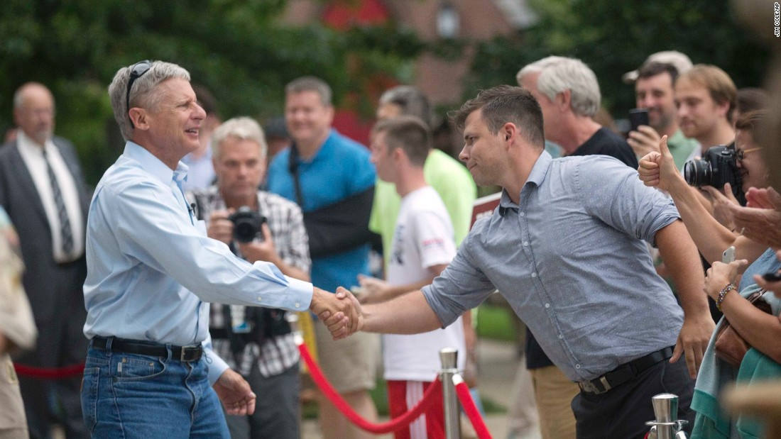 Libertarian presidential nominee Gary Johnson, left, shakes hands with a supporter as he arrives for a campaign rally in Concord, New Hampshire, on Thursday, August 25.