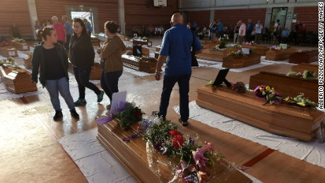 People stand next to the coffins of earthquake victims, in a gymnasium arranged in a chapel of rest on August 26, 2016, in Ascoli Piceno, two day after a 6.2-magnitude earthquake struck the region killing some 267 people. Italy on August 26, 2016 declared a day of mourning for victims of a devastating earthquake as hopes of finding any more survivors dwindled and the confirmed death toll rose to 267. Flags will fly at half-mast across the country on August 27 to coincide with funerals for some of the victims. Immacolata Postiglione, head of the Civil Protection agency's emergency unit, said no new survivors had been found overnight in the remote mountain villages blitzed by the powerful pre-dawn quake on August 24, 2016. / AFP / ALBERTO PIZZOLI        (Photo credit should read ALBERTO PIZZOLI/AFP/Getty Images)