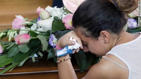 Relatives mourn near coffins of some of the earthquake victims prior to the start of the funeral service in Ascoli Piceno, Italy, Saturday, Aug. 27, 2016. Ahead of the funeral, caskets were lined up in a gym where mourners have been bidding farewell to loved ones, kneeling, crying and placing their hands on flower-covered caskets. (AP Photo/Andrew Medichini)