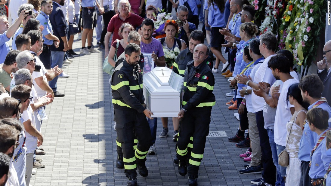 Firefighters carry the coffin of 9-year-old Giulia Rinaldo outside the gymnasium for the state funeral service for victims of the earthquake in Ascoli Piceno, Italy, Saturday, August 27.