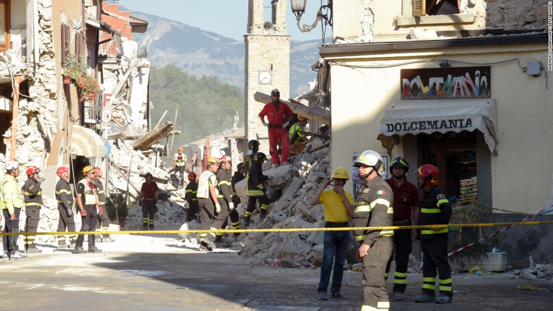 Firefighters and rescue workers stand near the damaged Sant'Agostino church and a destroyed ice cream shop in the Italian village of Amatrice on Friday, August 26.