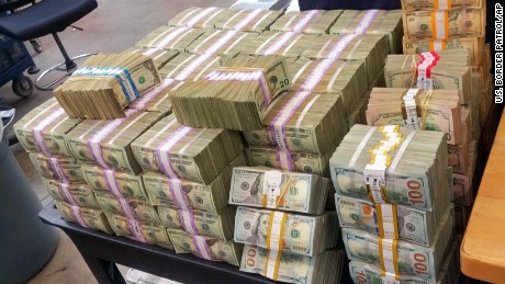 This Aug. 26, 2016 photo provided by the U.S. Border Patrol shows some of more than $3 million in cash that two men were trying to smuggle into Mexico from California. The agency says its agents tracked and stopped a Kia Forte in Escondido, Calif., on Tuesday, Aug. 23, and found nearly $34,000 stashed in the car's center console. Another car, a Volkswagen Passat, sped away, and when found a short time later had more than $3 million, shown here, packed in boxes in the trunk. (U.S. Border Patrol via AP)