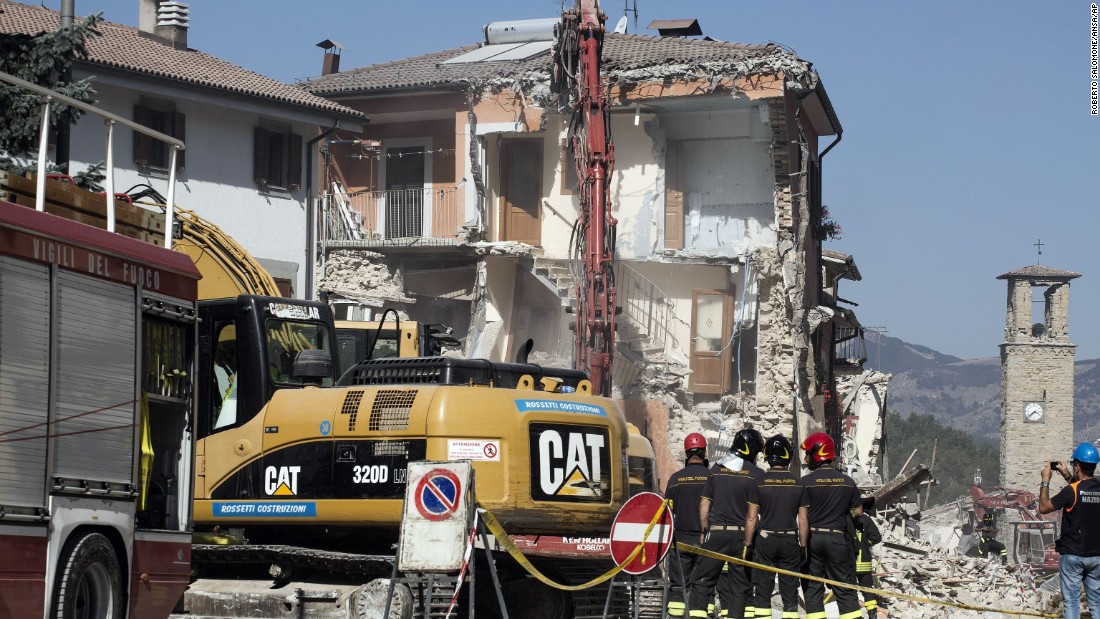 Firefighters stand by an excavator in Amatrice, Italy,on August 28, as dangerously damaged buildings and overhanging ledges are pulled down.