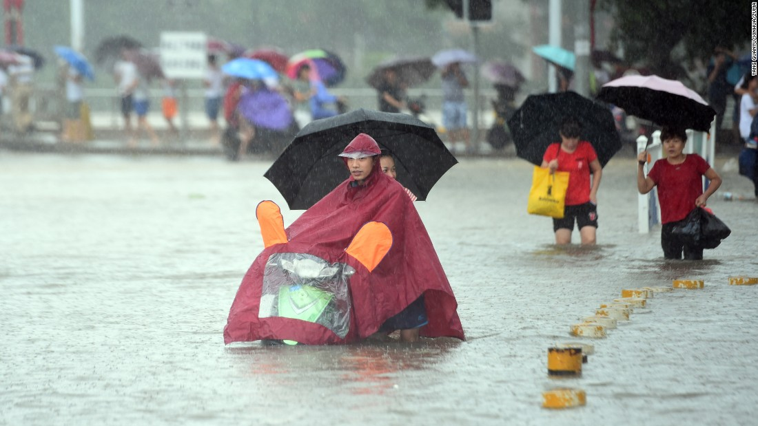 People wade through a waterlogged street in Lincheng Town, China, on Thursday, August 18. Typhoon Dianmu had brought heavy rain to the area.