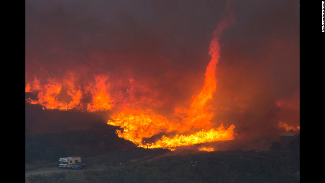 """A fire tornado forms near cars parked on a country road near Wrightwood, California, on Wednesday, August 17. <a href=""""http://www.cnn.com/2016/08/21/us/california-wildfires/"""" target=""""_blank"""">The Blue Cut wildfire</a> forced more than 80,000 people to evacuate the area."""