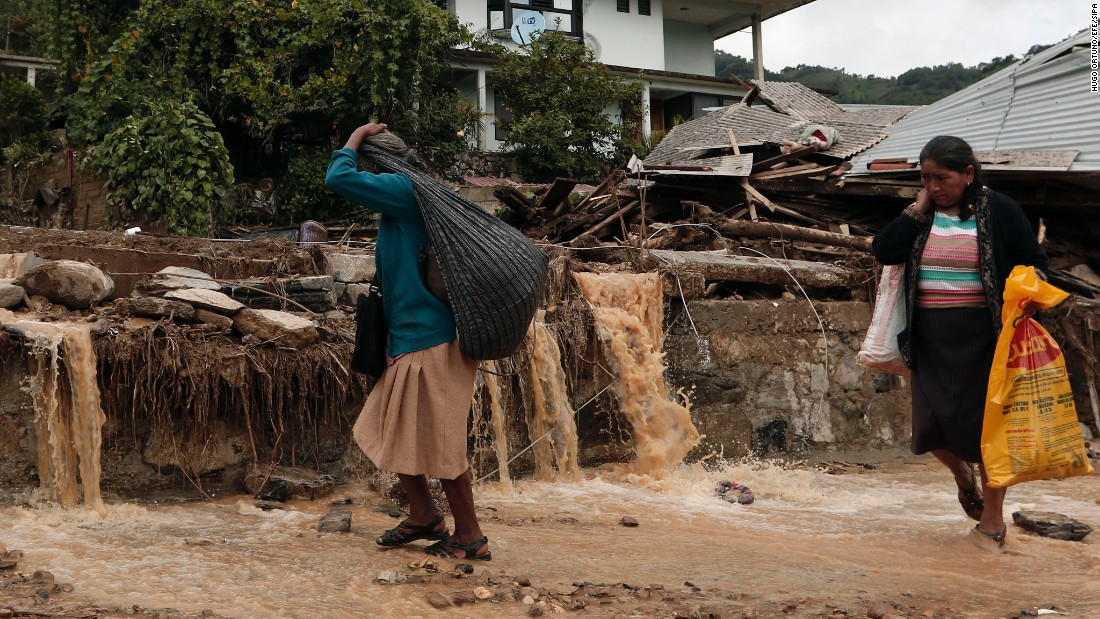 """Women walk in Huauchinango, Mexico, on Monday, August 8, after <a href=""""http://www.cnn.com/2016/08/07/world/mexico-landslides-deaths/"""" target=""""_blank"""">landslides caused by Tropical Storm Earl.</a>"""