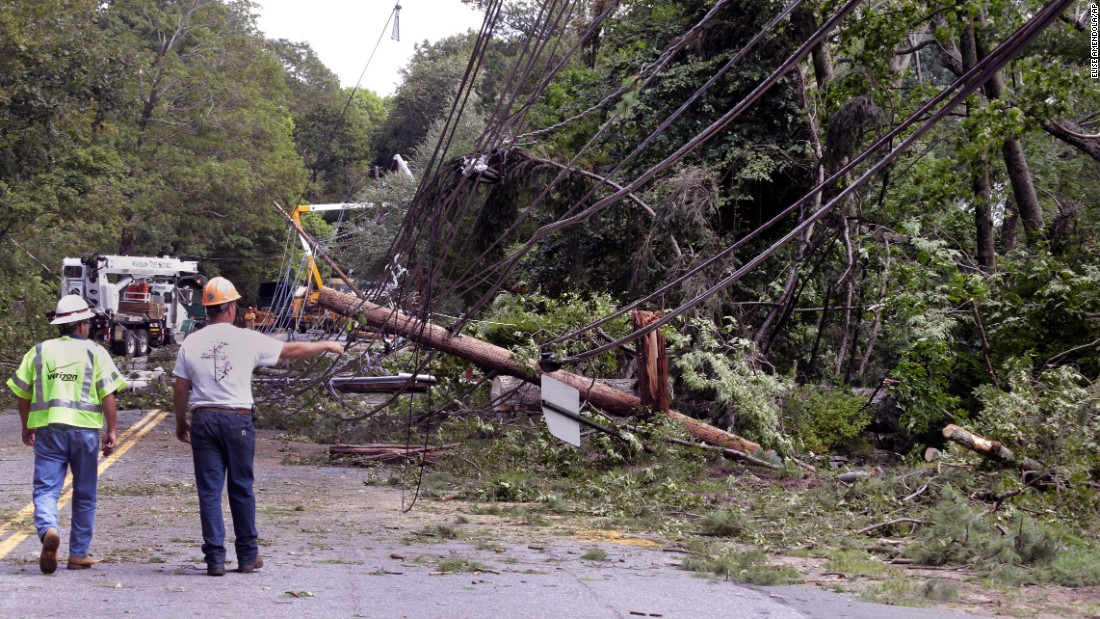 Workers observe downed trees and power lines Monday, August 22, after a tornado touched down in Concord, Massachusetts.
