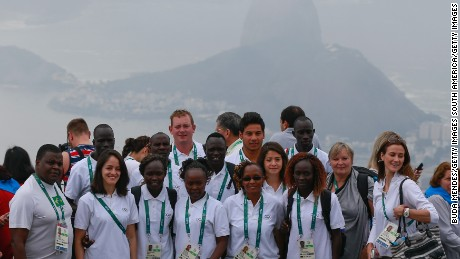 RIO DE JANEIRO, BRAZIL - JULY 30:  Members of the Olympic refugee team pose at the statue of Christ the Redeemer with the Sugar Loaf mountain behind them on July 30, 2016 in Rio de Janeiro, Brazil. A group of 10 athletes from South Sudan, Syria, Congo and Ethiopia will compete in Rio under the Olympic flag.  (Photo by Buda Mendes/Getty Images)