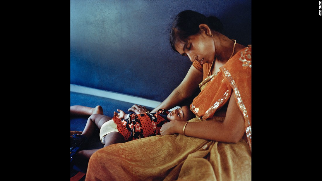 A mother rests with her baby on the third and final day of their train trip to Kerala.