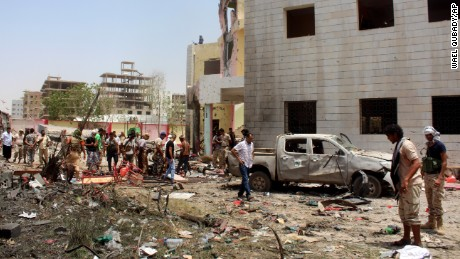 Fighters loyal to the government gather at the site of a suicide car bombing in Yemen's southern city of Aden, Yemen, Monday, Aug. 29, 2016. The bombing claimed by the Islamic State group in Aden has killed over 50 pro-government troops who had been preparing to travel to Saudi Arabia to fight Houthi rebels in Yemen's north. Yemen is embroiled in a civil war pitting the internationally recognized government and a Saudi-led coalition against the Shiite Houthi rebels, who are allied with army units loyal to a former president. The fighting has allowed al-Qaida and an IS affiliate to expand their reach, particularly in the south. (AP Photo/Wael Qubady)
