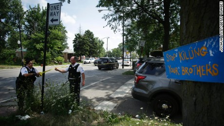 """CHICAGO, IL - JULY 27: A sign that reads """"Stop Killing Your Brothers"""" is displayed from a tree as Chicago Police officers hang yellow crime scene tape where a man was shot multiple times as he sat in a vehicle July 27, 2016 in Chicago, Illinois. Over 2,000 people have been shot across Chicago and hundreds of people killed since the start of the year. (Photo by Joshua Lott/Getty Images)"""
