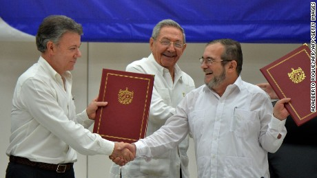 "Colombia's President Juan Manuel Santos (L) and Timoleon Jimenez, aka ""Timochenko"" (R), head of the FARC leftist guerrilla, shake hands accompanied by Cuban President Raul Castro (C) during the signing of the peace agreement in Havana on June 23, 2016. Colombia's government and the FARC guerrilla force signed a definitive ceasefire Thursday, taking one of the last crucial steps toward ending Latin America's longest civil war. / AFP / ADALBERTO ROQUE        (Photo credit should read ADALBERTO ROQUE/AFP/Getty Images)"