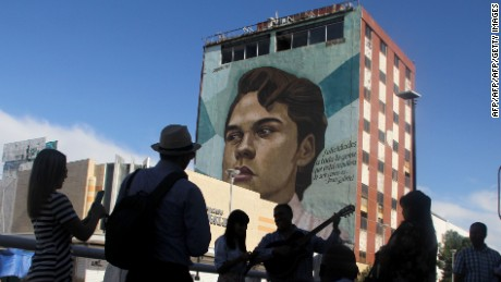 "People sing next to a building with a mural depicting the face of Mexican singer Juan Gabriel, in Ciudad Juarez, on August 28, 2016.  Mexican singer, composer and producer Alberto Aguilera Valadez, better known as ""Juan Gabriel"", died on August 28, 2016 in Santa Monica, California, U.S.A. from a heart attack / AFP / HERIKA MARTINEZ        (Photo credit should read HERIKA MARTINEZ/AFP/Getty Images)"