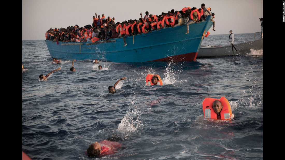Migrants, most of them from Eritrea, jump into the Mediterranean from a crowded wooden boat during a rescue operation about 13 miles north of Sabratha, Libya, on August 29.