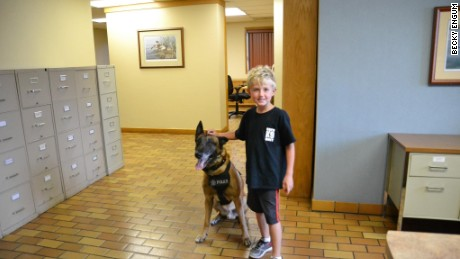 Ethan Engum poses with a police dog at K9 training