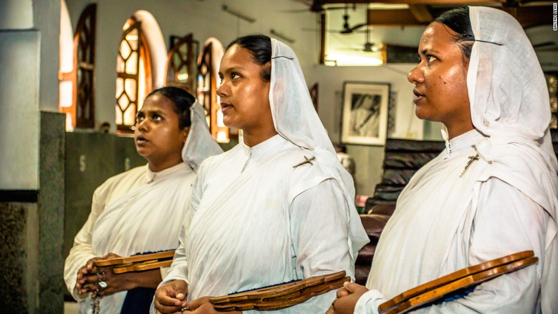 Novice nuns stand and pray before they start their work at the Home for the Dying and Destitute.