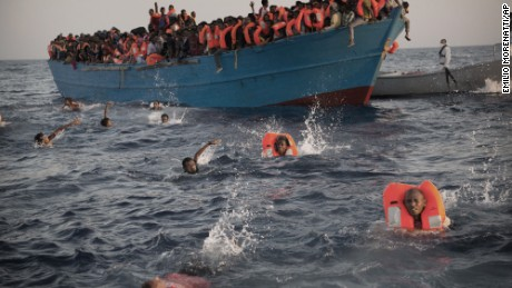 Migrants, most of them from Eritrea, jump into the water from a crowded wooden boat as they are helped by members of an NGO during a rescue operation at the Mediterranean sea, about 13 miles north of Sabratha, Libya on Monday, August 29, 2016.