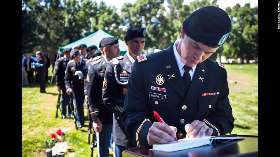 U.S. Army 2nd Lt. Thomas Mitchell, of the Fort Carson Military Funeral Honors Team, signs a guestbook Saturday, August 13, following a graveside service for Navy Ensign John Charles England in Colorado Springs, Colorado. England was killed aboard the USS Oklahoma during the attack on Pearl Harbor, and he had been buried at the National Memorial Cemetery of the Pacific until his remains were identified and reburied in Colorado.