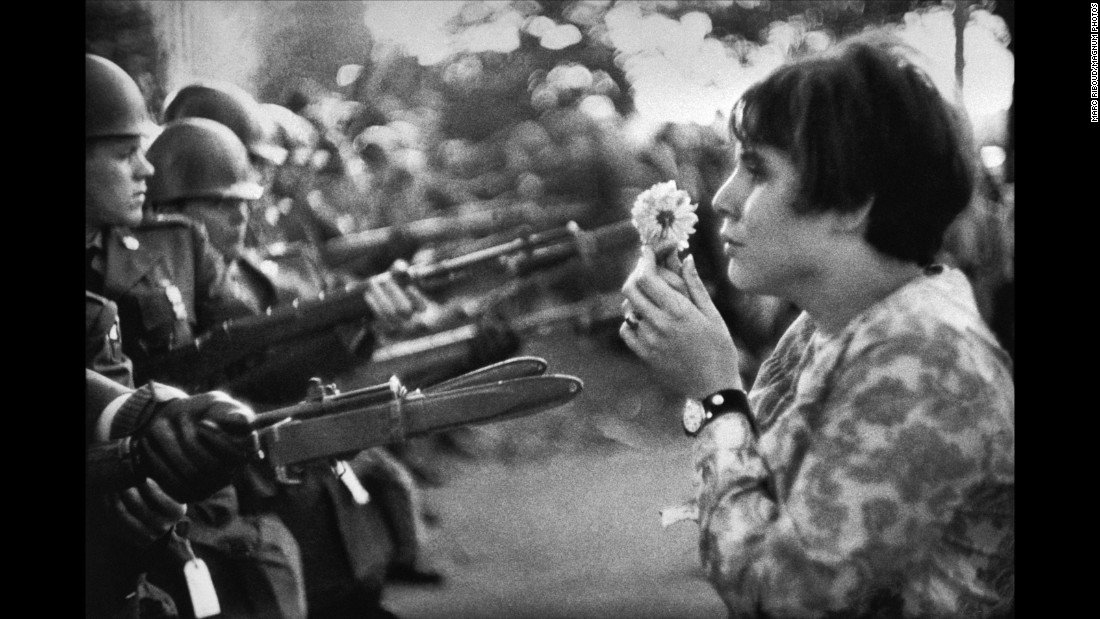 """Jan Rose Kasmir confronts National Guard troops with a flower during a Vietnam War protest outside the Pentagon in 1967. This is one of the most memorable anti-war images from that era. It was taken by Marc Riboud, an acclaimed French photographer who died this week at the age of 93. """"She was just talking, trying to catch the eye of the soldiers, maybe try to have a dialogue with them,"""" Riboud recalled in the April 2004 issue of Smithsonian magazine. """"I had the feeling the soldiers were more afraid of her than she was of the bayonets."""""""