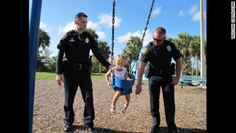 The officers who helped save Kennedy's life reunite with her at the swingset.