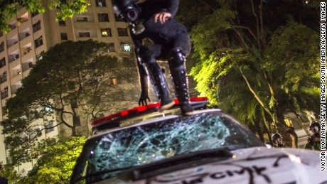 A protester jumps on a police vehicle during a march against the Senate vote Wednesday in Sao Paulo.