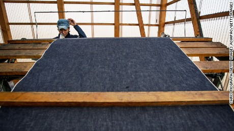 A man works a weaving machine at the Momotaro Jeans factory in Kojima district, Okayama.