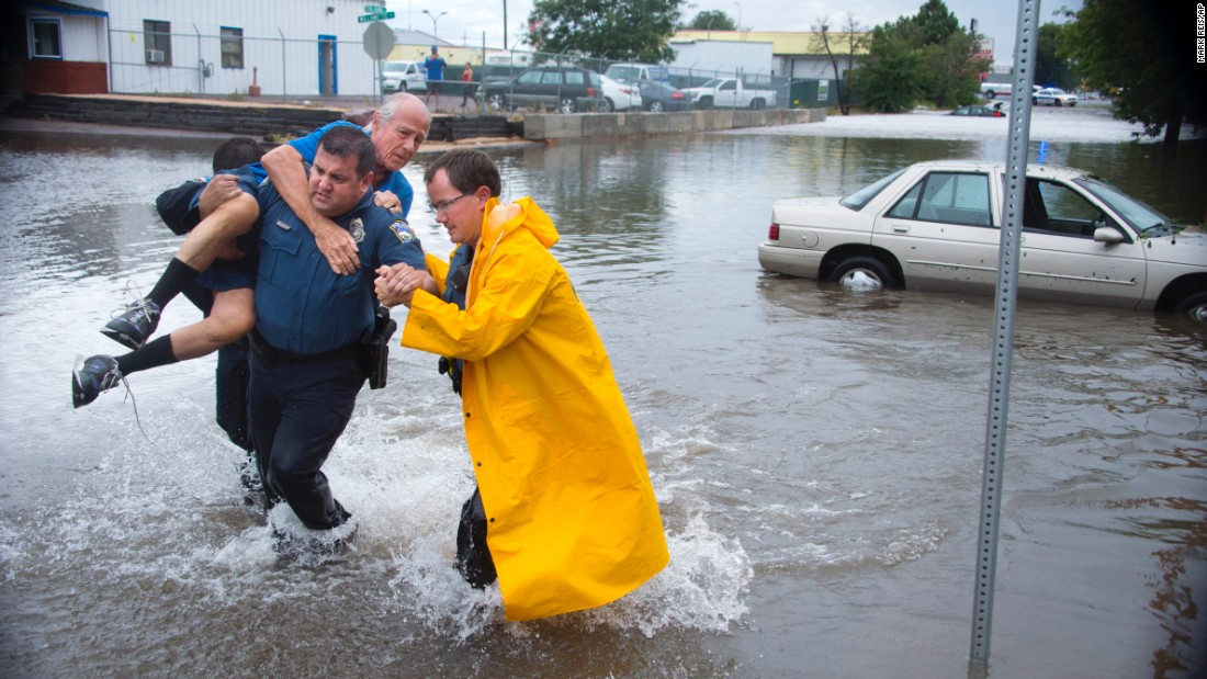 Eric Reed, a police officer in Colorado Springs, Colorado, carries a motorist who was stranded in a flooded intersection on Monday, August 29.