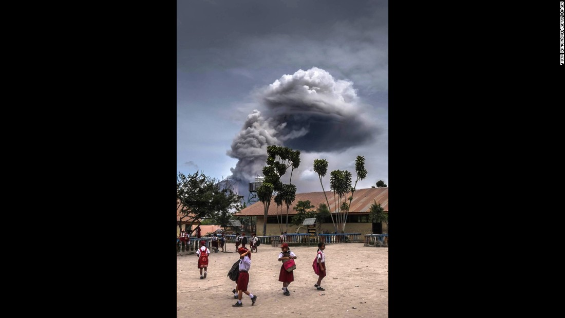 Students play in Karo, Indonesia, as Mount Sinabung spews thick volcanic ash on Tuesday, August 30.