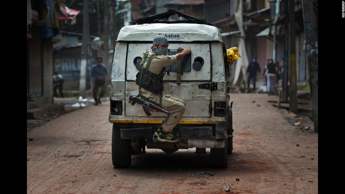 An Indian police officer takes cover behind an armored vehicle as Kashmiri protesters throw stones at him during a protest in Srinagar, India, on Tuesday, August 30. Anti-India protests erupted in several neighborhoods after authorities lifted a curfew imposed in most parts of Indian-controlled Kashmir.