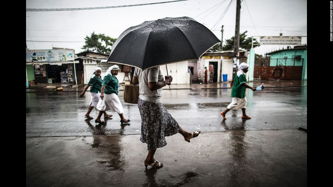 A woman washes her foot with water streaming out of a pipe as nuns leave a church in Libreville, Gabon, on Sunday, August 28.