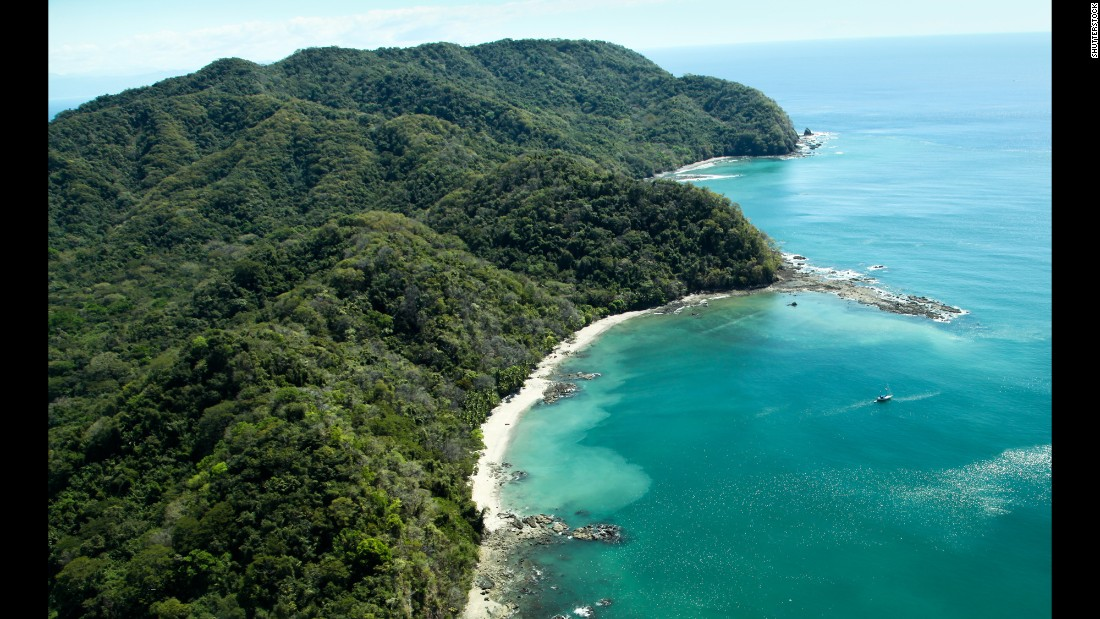 Lush jungle-covered mountains stretch out into the Gulf of Nicoya next to the rocky and sandy beach of Ballena Bay in Costa Rica.